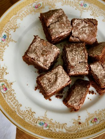 brownies dusted with powded sugar and cocoa on a gold-rimmed plate with a white linen napkin