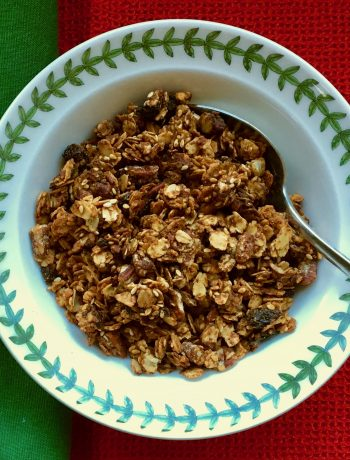 granola in a white bowl rimmed with green on a green and red cloth