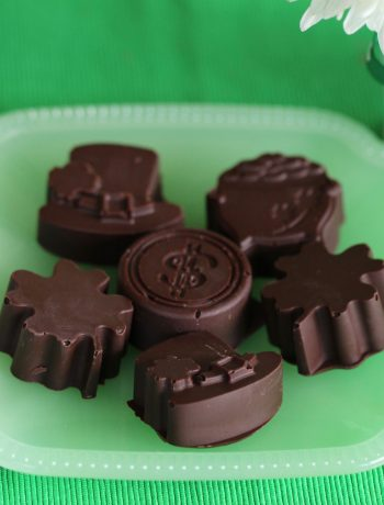 dark chocolate nut butter cups in St. Patrick's Day shapes on green plate on green cloth