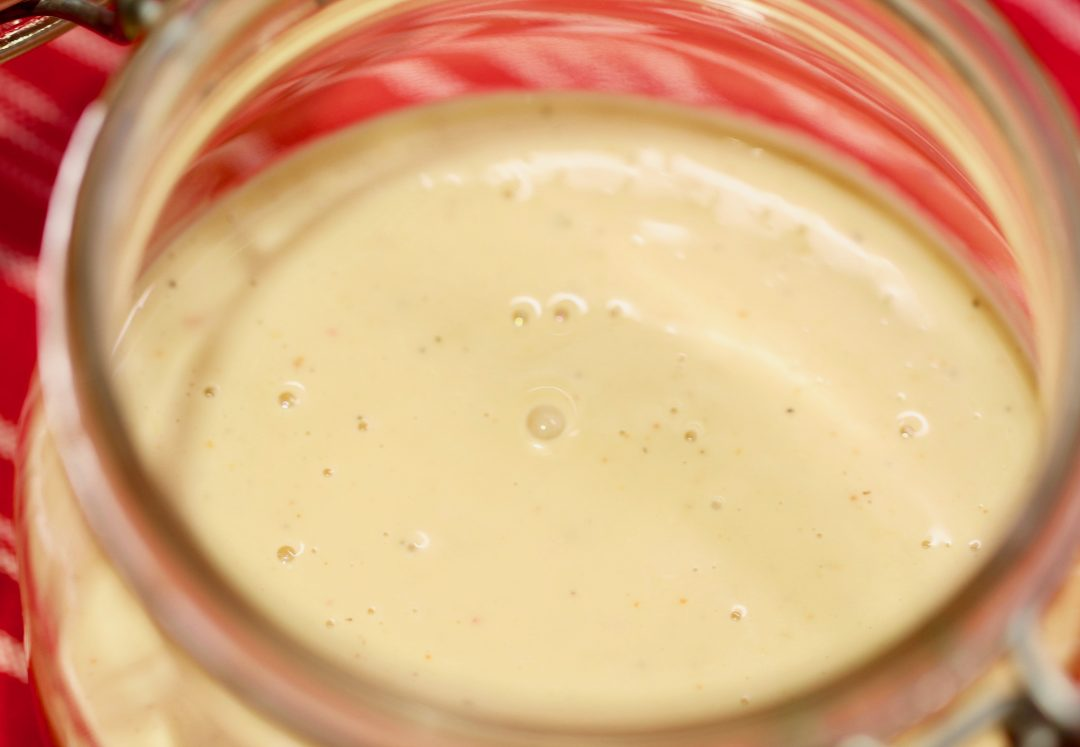 white barbecue sauce in glass jar on red cloth