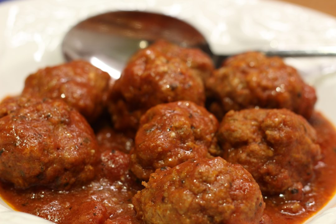 meatballs with a silver spoon on a white plate