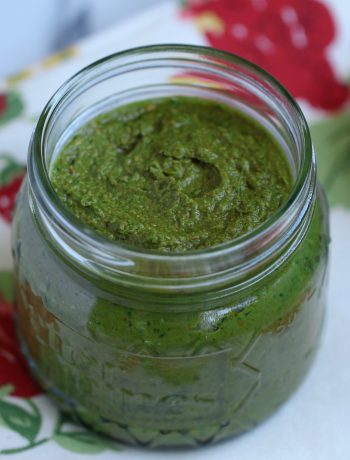 kale cashew pesto in a glass jar on a white and red cloth