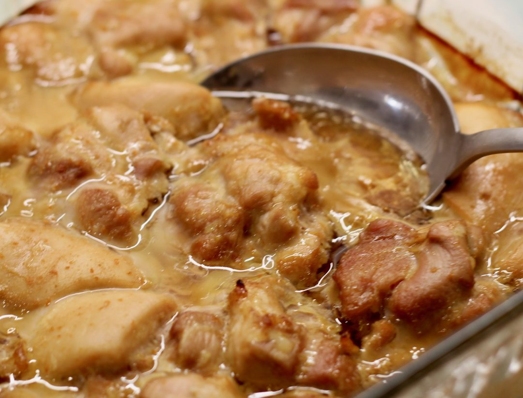 cooked chicken thighs with orange teriyaki sauce in a glass baking dish with a stainless steel serving spoon