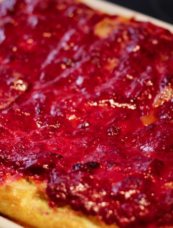 baked raspberry french toast in a ceramic baking dish on a black surface