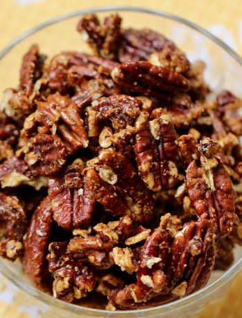 honey chipotle pecans in a glass dish on a yellow cloth
