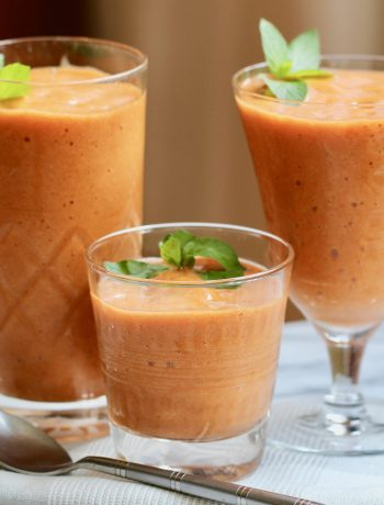 fresh apricot smoothie with mint in three glasses on a marble top