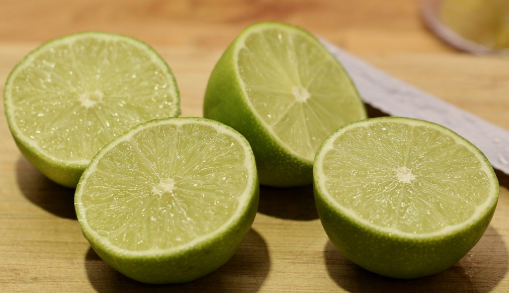 four half limes on a wood board with a knife