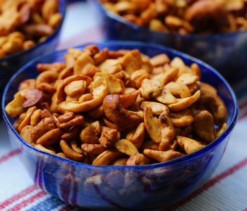lime chipotle cashews in a blue glass bowl on a red white and blue cloth