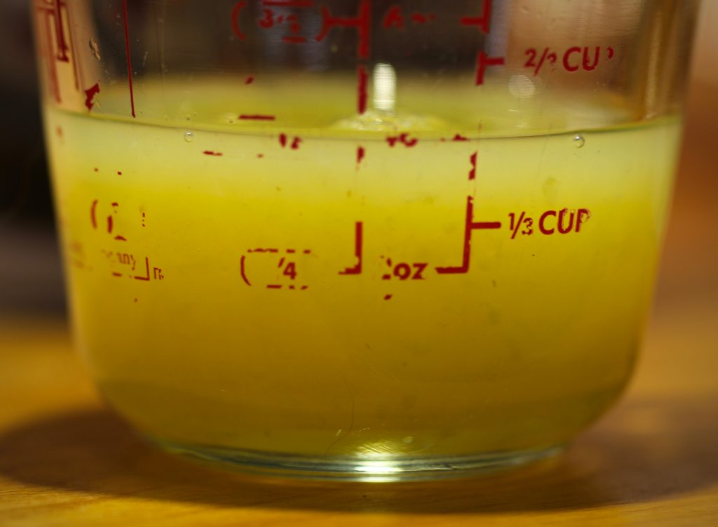 half a cup of lemon juice in a measuring cup on a wooden counter