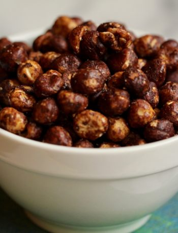 cocoa coated toasted hazelnuts piled high in a white ceramic bowl on a blue and green cloth