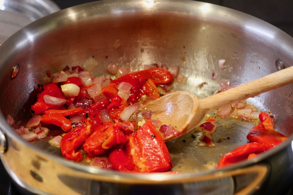 red peppers sautéing in a stainless steel pan with a wooden spoon