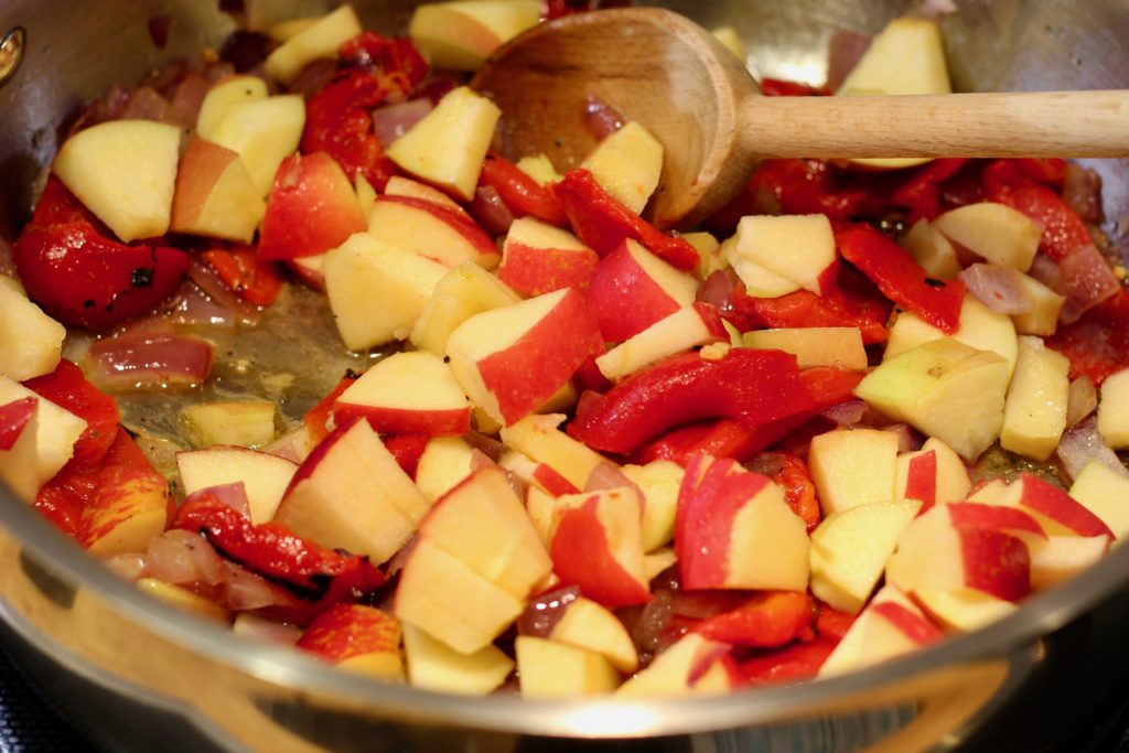 apples added to the pan of pumpkin soup in a stainless steel pan
