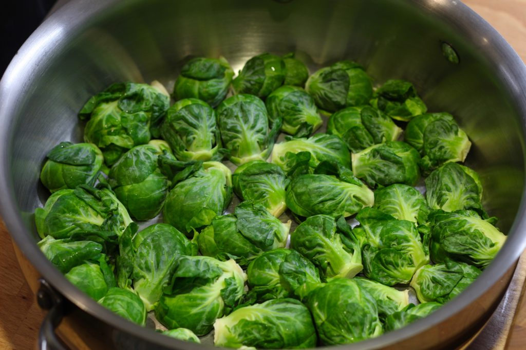 sliced Brussels sprouts in the bottom of a stainless steel pan