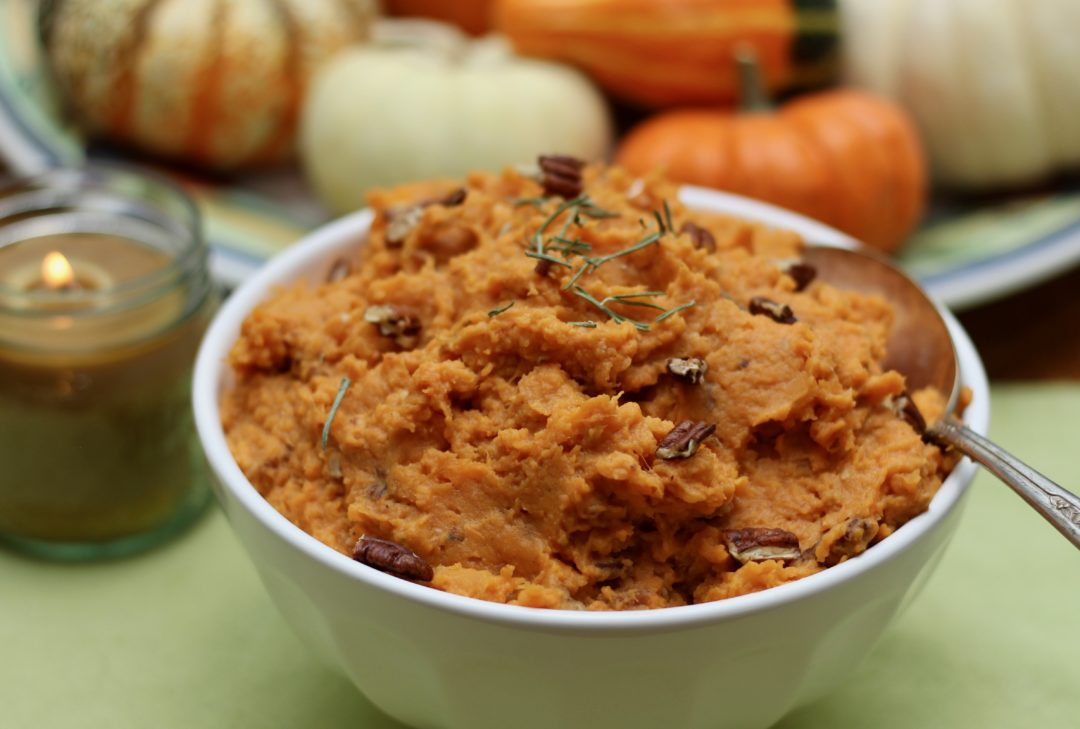 mashed sweet potatoes with rosemary and pecans in a white bowl with a silver spoon on a green cloth with a candle and plate of pumpkins in the background 2