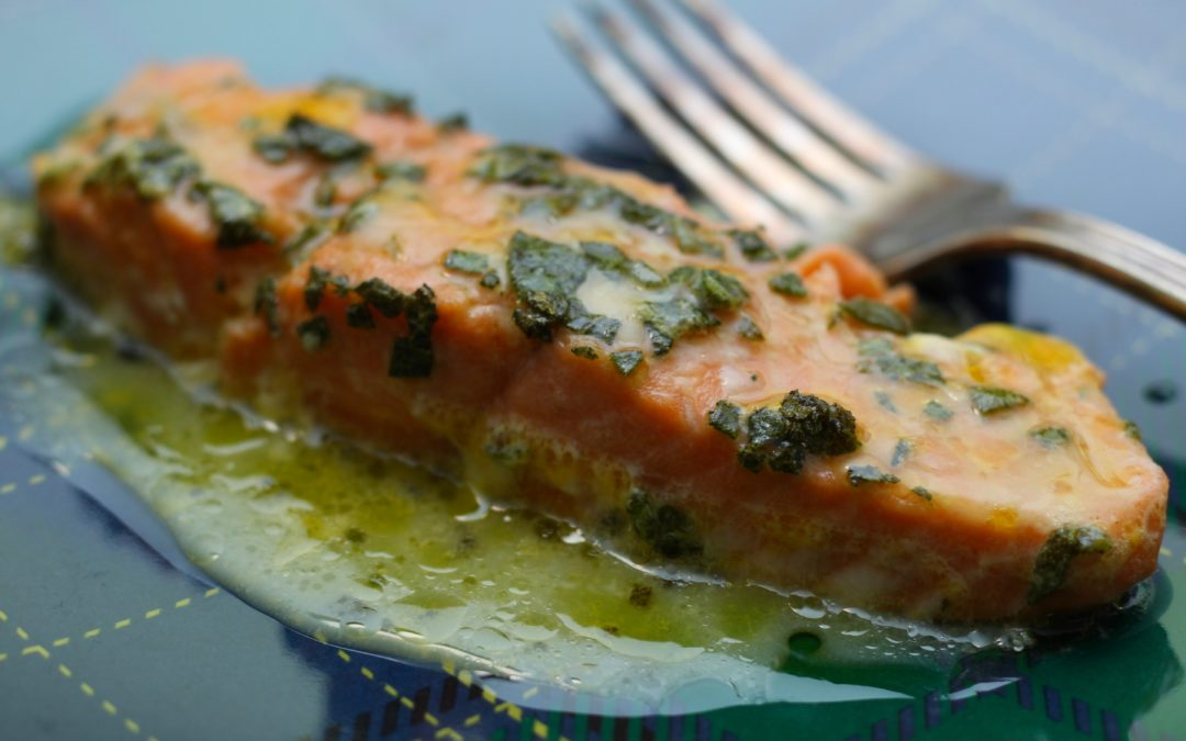 salmon baked with orange sage sauce on a blue plate with a silver fork 2