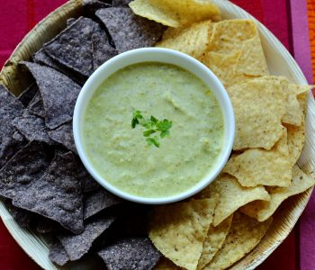 roasted shishito pepper dip in a white bowl on a platter surrounded by yellow and blue corn chips