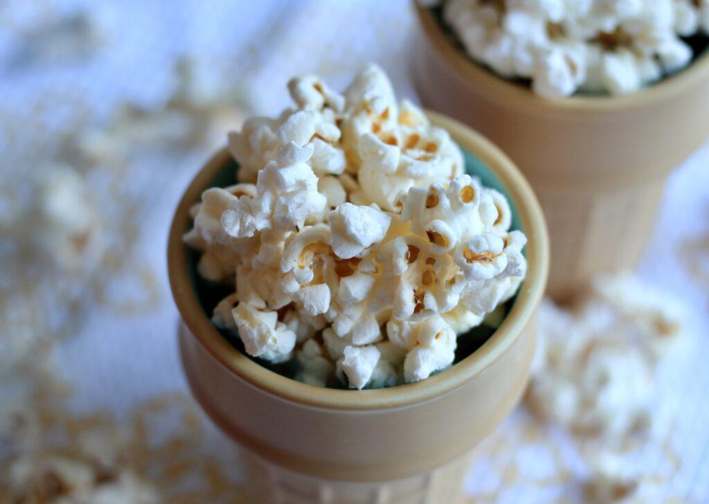 popcorn in a ceramic ice cream cone on a white and yellow cloth