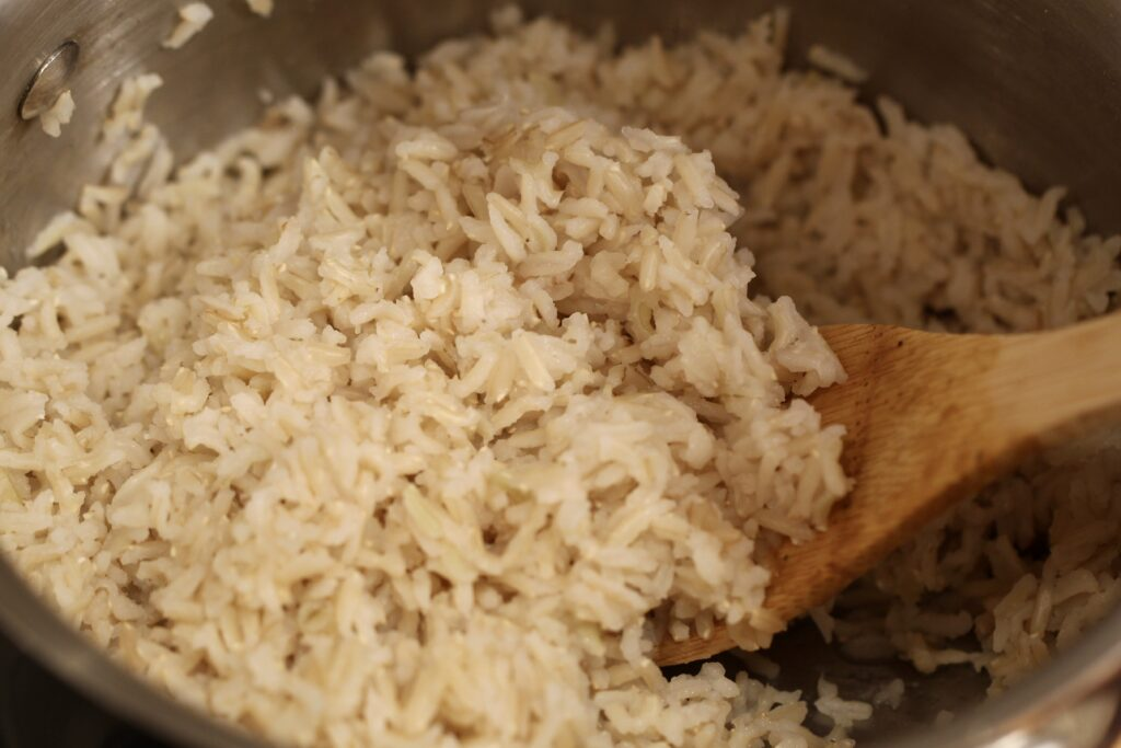 brown rice in a pan with a wooden spoon