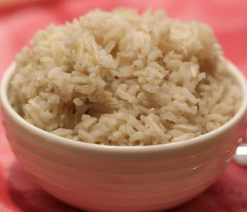 brown rice in a white bowl on a red cloth