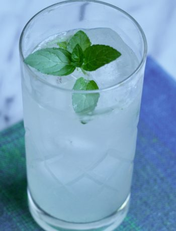 mint rosemary lime cooler in a tall glass on a blue cloth garnished with mint