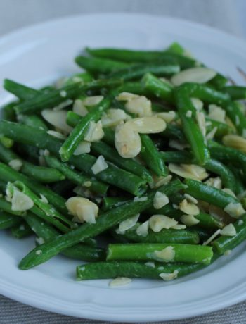 green beans with garlic and almonds on a white plate
