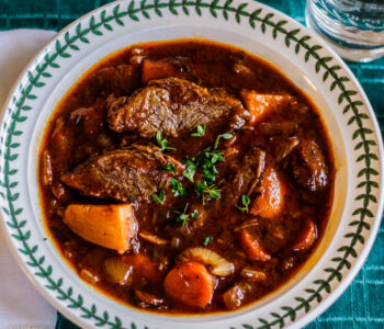 pot roast in a white bowl on a green cloth with a white napkin