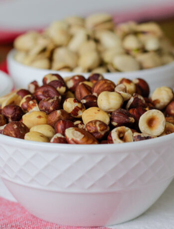 bowls of hazelnuts, cashews in white bowls on a red and white cloth