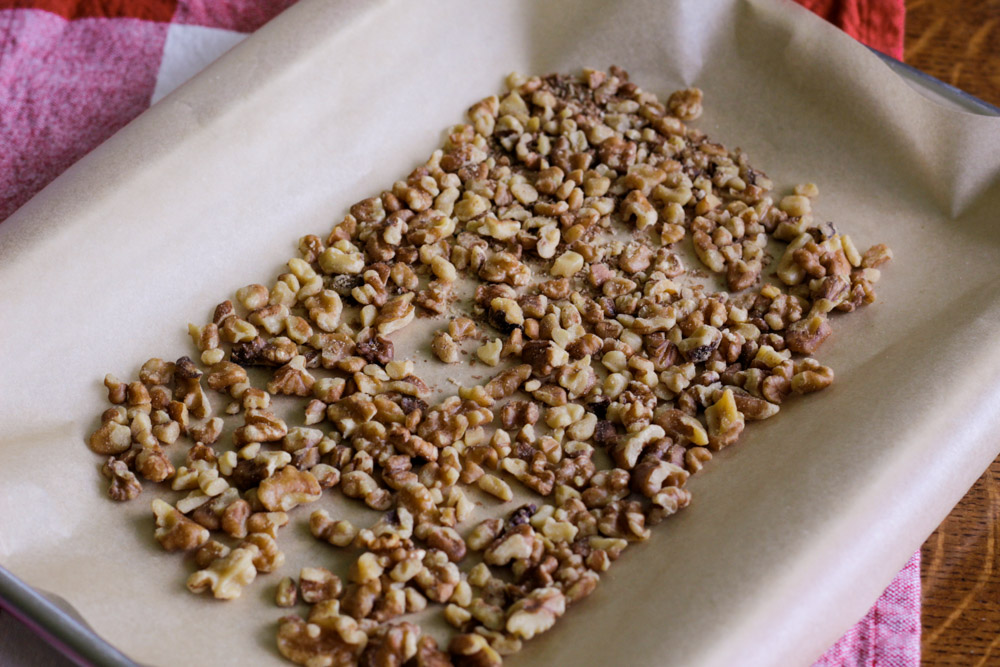 walnuts on parchment on a baking sheet