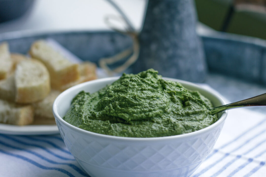 vegan pesto sauce in a white bowl on a blue and white cloth